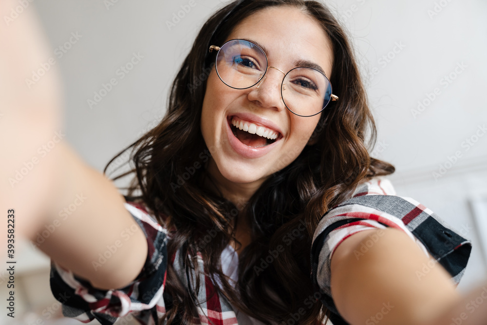 Fototapeta Cheerful nice woman in eyeglasses smiling and taking selfie photo