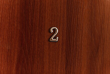 Golden Number Two Sign On Brown Door Of Apartments. Closeup.