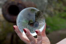 Woman Holding Crystal Ball With Reflection Of Cannon