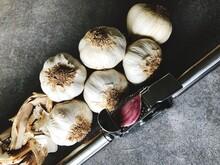 High Angle View Of Garlic And Garlic Press On Table