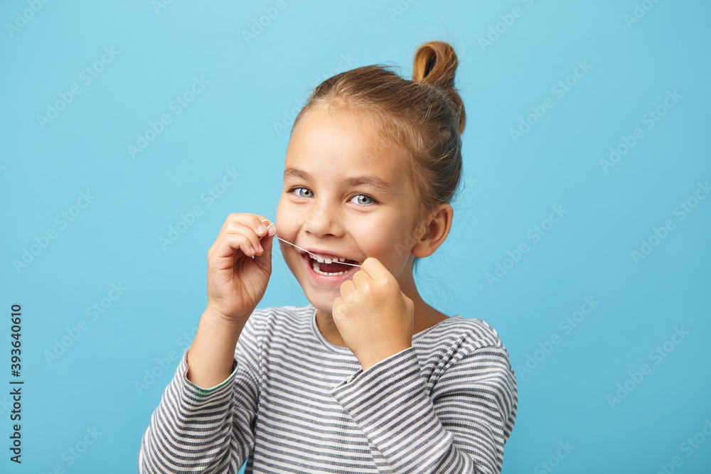 Fototapeta Dental flush, caucasian child girl using flossing teeth and smiling