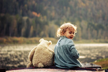 A Smiling Baby Girl Is Sitting On An Old Boat With Her Teddy Bear On A Mountain River Bank In Autumn