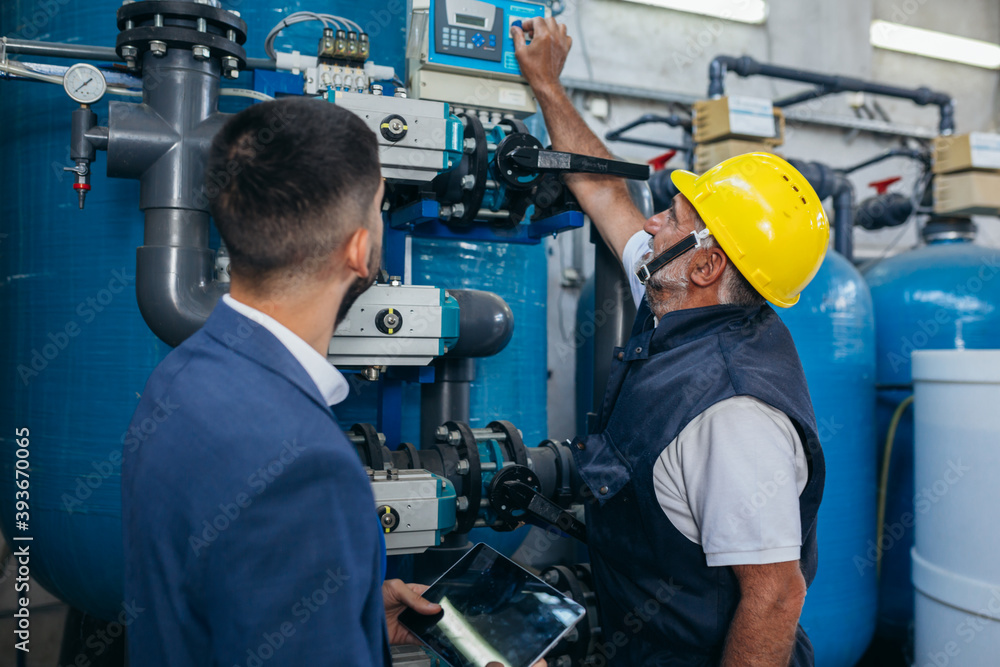 Fototapeta industrial worker inspecting chemical treatment equipment
