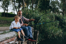 Boy Fishing On The Lake With His Grandfather
