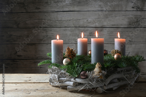 Rustic advent wreath of wood, fir branches and Christmas decoration with four burning candles against a gray wooden wall with copy space