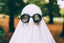 Child Wearing Sheet And Goggles Ghost Halloween Costume