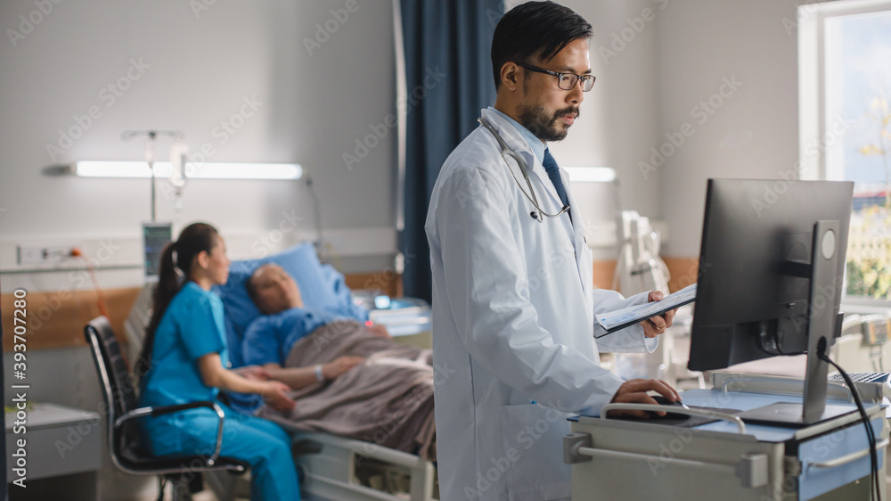 Fototapeta Hospital Ward: Professional Experienced Chinese Doctor Surgeon Uses Medical Touchscreen Computer to Check Test Results. In Background Head Nurse Sitting with Patient Recovering After Surgery in Bed
