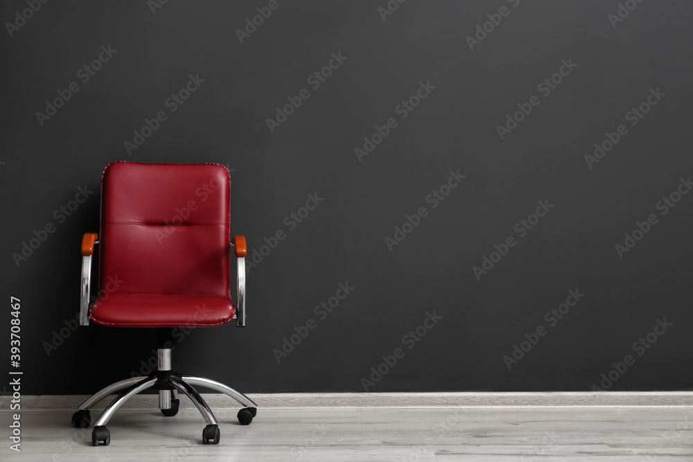 Fototapeta Comfortable office chair near black wall indoors. Space for text