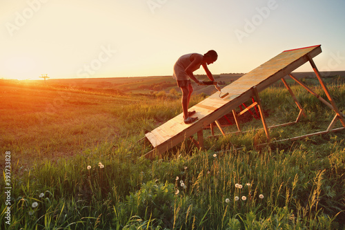 Young Caucasian man paints new mtb gap in the field at sunset Canvas