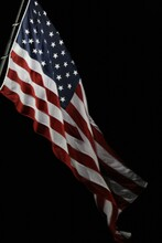 Low Angle View Of American Flag Against Black Background