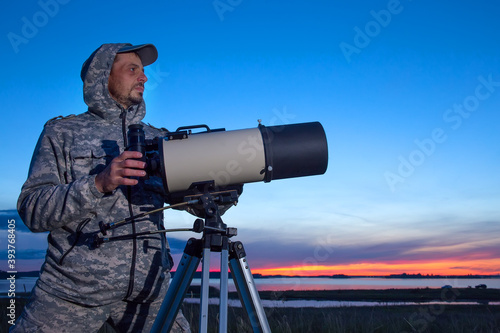 Foto A male astronomer observes the sky through a telescope