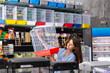 Portrait of young attractive brunette choosing birdcage in pet shop
