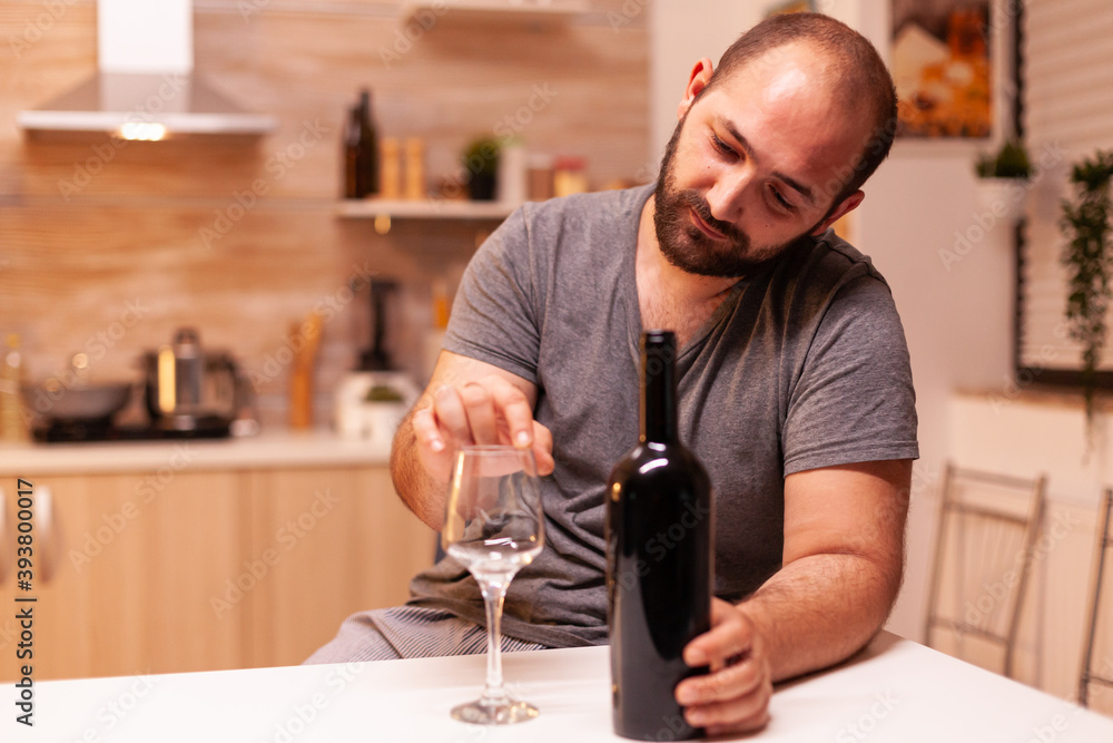 Fototapeta Alcoholic man being depressed and frustrated holding bottle of red wine in kitchen. Unhappy person disease and anxiety feeling exhausted with having alcoholism problems.