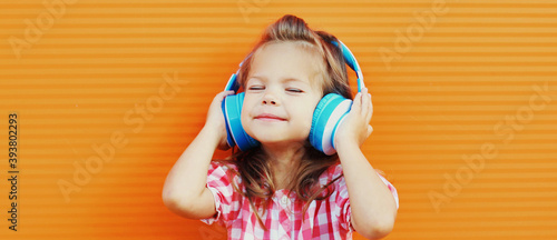 Portrait of little girl child in wireless headphones listening to music over orange background