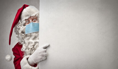Santa Claus with mask points on a white billboard