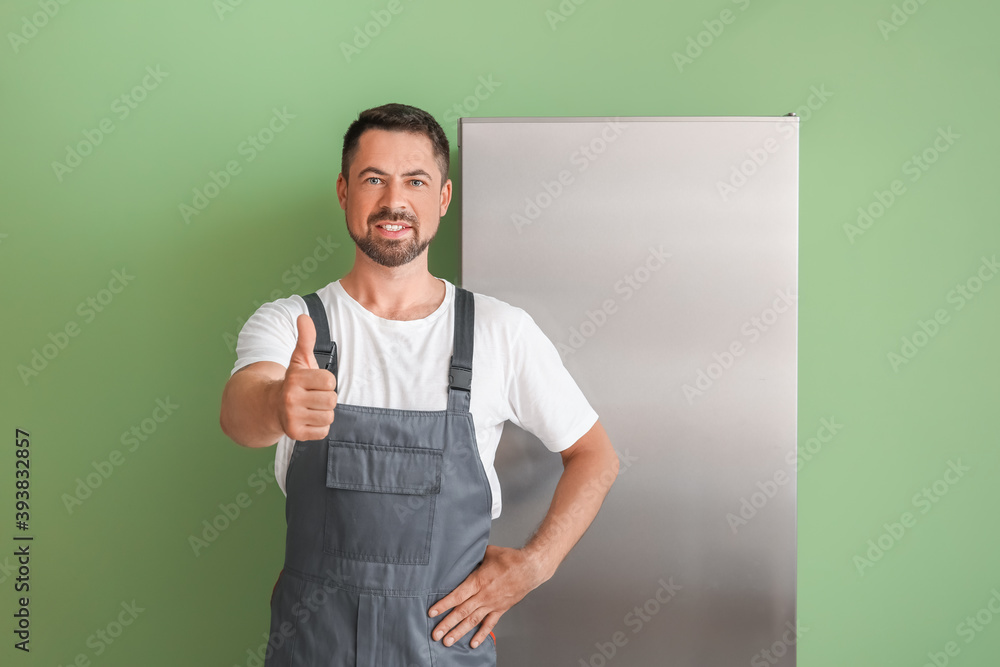 Fototapeta Worker of repair service showing thumb-up near fridge on color background