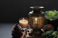 Aroma Essential Oil Brass Burner Are Put On The Wooden Slats On Black Table With Candles Decorated  By Pinecone And Potpourri Anise Star And Dried Spices In The Luxurious Day Spa Resort Hotel