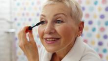 Mature Woman Putting Mascara L...