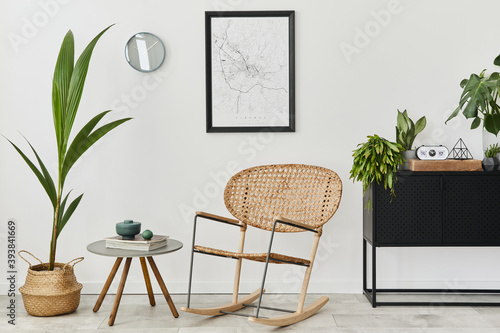 Modern retro concept of home interior with design rattan armchair, coffee table, commode, plants, mock up poster map, decoration and personal accessoreis. Stylish home decor of living room.