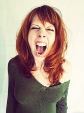 Portrait Of Woman Screaming While Standing Against White Background