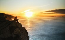 Man Sitting On Rocks By Sea Against Sky During Sunset