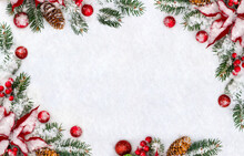 Christmas Decoration. Frame Of Branches Christmas Tree, Flowers Of Red Poinsettia, Brown Natural Spruce Cones, Red Ball, Red Berries On Snow With Space For Text. Top View, Flat Lay