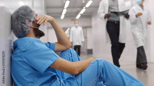 Photo Upset and tired surgeon sitting on floor in hospital corridor