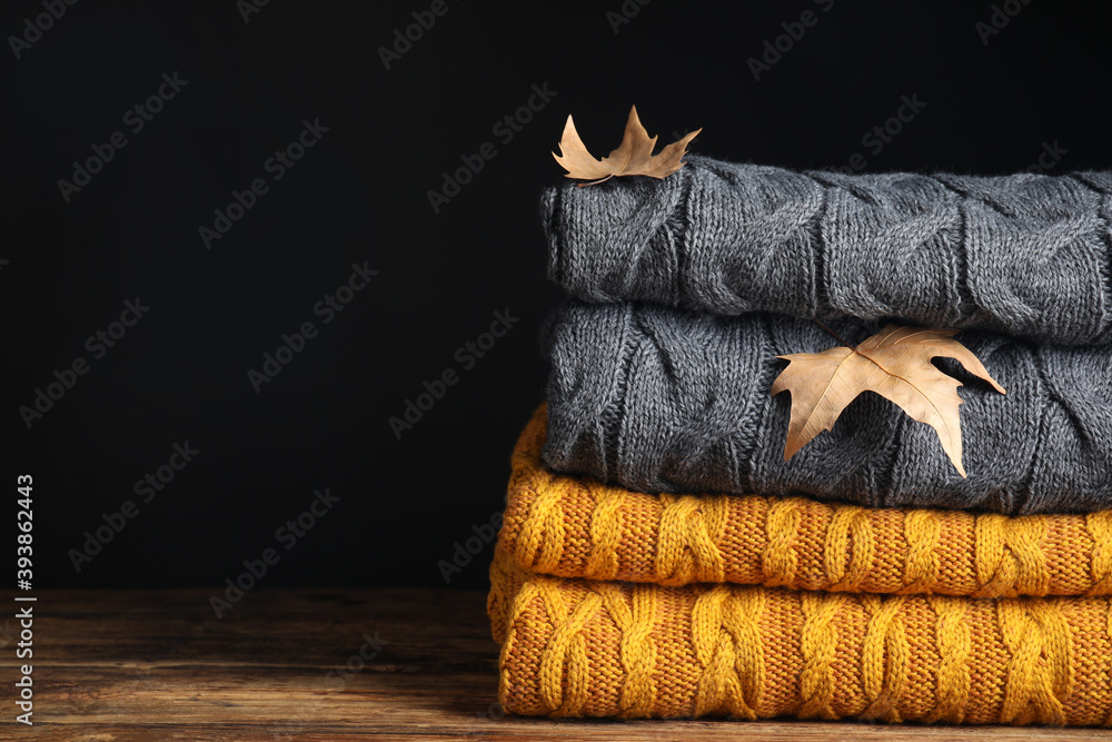 Fototapeta Grey and orange knitted plaids with dry leaves on wooden table, closeup. Space for text