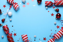 Frame Of Christmas Crackers And Decorations On Light Blue Background, Top View With Space For Text