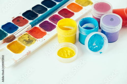 Colorful gouache paints and brush for painting on white background Canvas Print