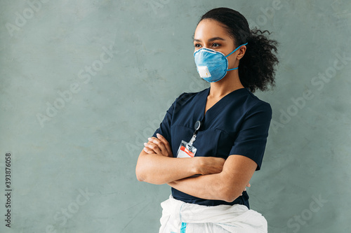 Fotografiet Female nurse wearing a medical respirator and uniform standing at wall with arms