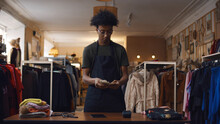 Young African Male Cashier Counting Chash On Modern Second-hand Store