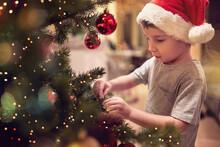 A Little Kid Ornamenting A Chr...