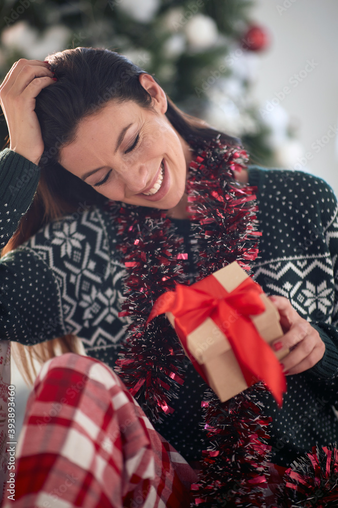 Fototapeta A young girl at home watching a Xmas present she got. Christmas, relationship, love, together