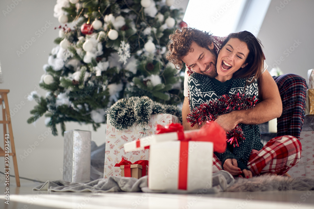 Fototapeta A young couple in love enjoying Christmas morning at home. Christmas, relationship, love, together
