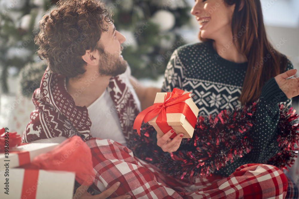 Fototapeta A young couple has romantic moments at home sharing Xmas presents. Christmas, relationship, love, together