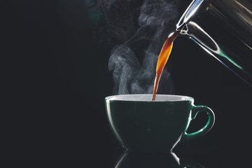 Pouring of hot coffee in cup on dark background