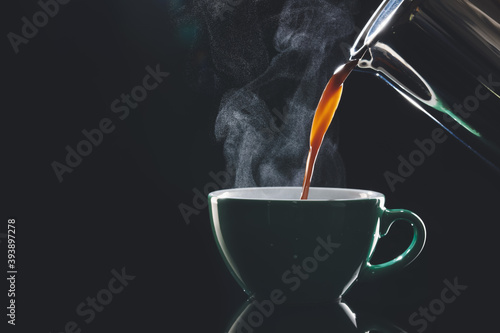 Fototapeta Pouring of hot coffee in cup on dark background