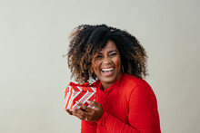 Portrait Of A Happy Mid Woman Laughing And Holding Red Christmas Gift Box