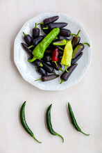 Plate Pile Of Various Chile Cultivars. Some (purple Jalapeno) With Dark Purple Color.