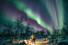 Man Holding A Lantern And Watching Northern Lights In Snowy Scenery