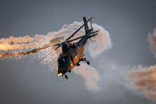 Army Helicopter In Flight Firing Off Defensive Flare Decoys At Dusk.