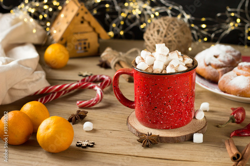a red mug with marshmallows inside is on the table Fototapete