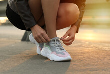 Woman Tying Laces On Sneakers ...
