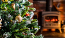 Close Up Of Christmas Tree Bobbles With Blured Out Fire In Background. Home Living Room Shallow Depth Of Field