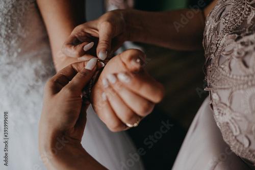 Panna młoda zakłada biżuterię bransoletkę do ślubu