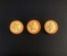 Three Round Baked Pies With Golden Pastry. Each Pie Is Decorated With Stars On It. Black Background