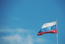 Low Angle View Of Russian Flag Against Blue Sky