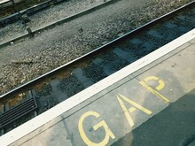 Mind The Gap Print In Yellow Next To Railway Tracks