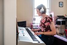 Woman Playing Piano Keyboard At Home